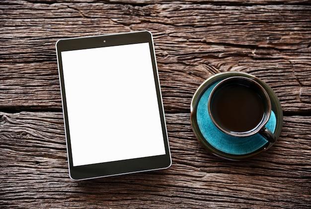 Tablette und kaffee des draufsichtleeren bildschirms auf holztisch mit kopienraum.