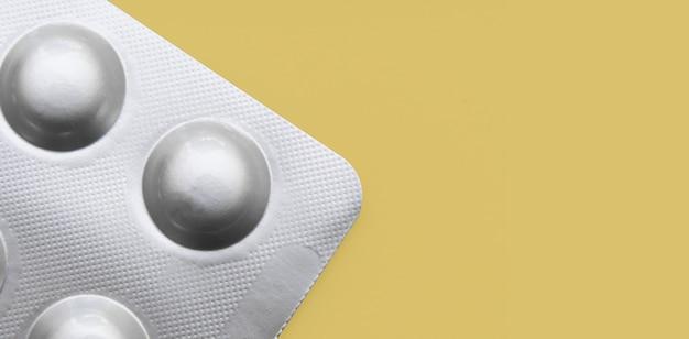 Tabletten in einer silbernen blisterpackung auf gelbem grund
