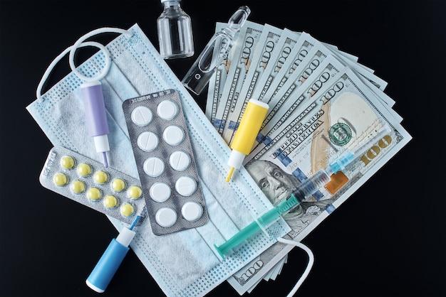 Tabletten, schutzmaske, medizinische artikel und dollarnoten im dunkeln.