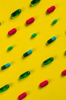 Tabletten und pillen in verschiedenen formen und farben auf gelbem untergrund. medizin.