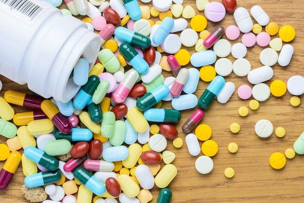 Tablettenfläschchen, das an pillen verschüttet, um hölzern aufzutauchen