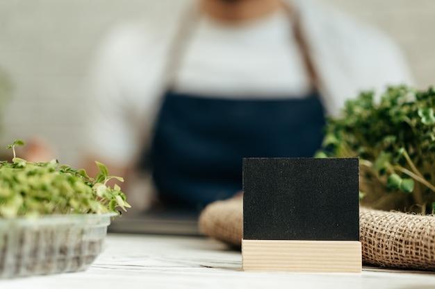Tabletts mit microgreens auf tisch mit kleinem schwarzem typenschild mit kopierraum