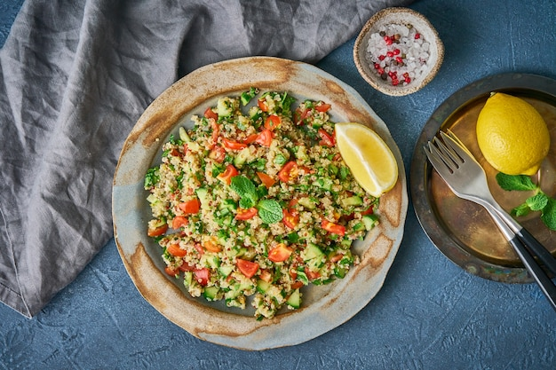 Taboulé-salat mit quinoa. östliches essen mit gemüsemischung auf dunkelheit