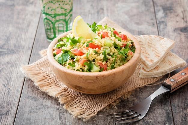 Tabouleh-salat mit couscous- und pittabrot in der hölzernen schüssel auf rustikaler tabelle