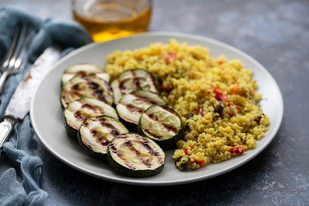 Tabouleh und gegrillte zucchini auf weißem teller