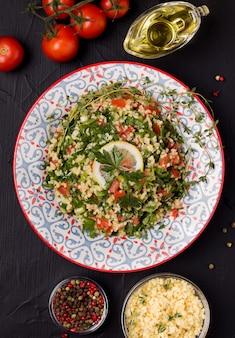 Tabule - ein orientalischer salat auf schwarzem grund neben den zutaten.