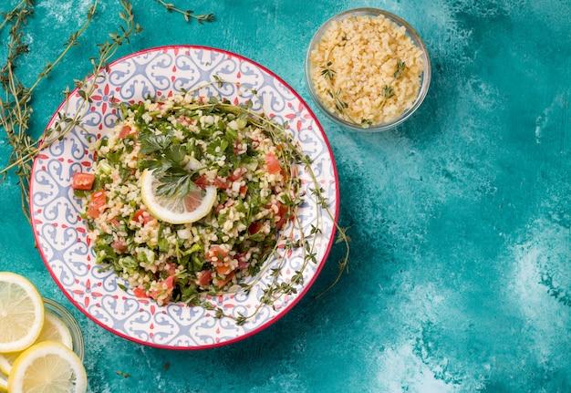 Tabule - ein orientalischer salat, eine vorspeise auf blauem grund neben zitrone und bulgur.