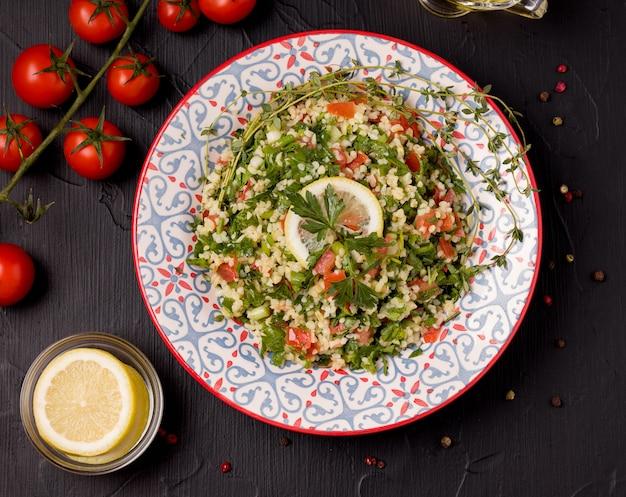 Tabule - orientalischer salat, nah an den zutaten und auf einem schwarzen tisch