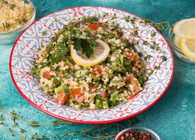 Tabule - orientalischer salat, vorspeise auf einem blauen hintergrund nahaufnahme neben den zutaten