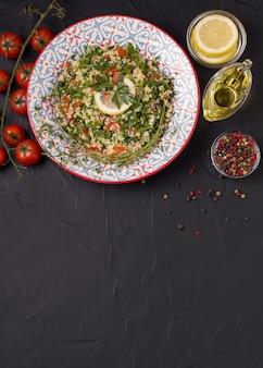 Tabule - orientalischer salat, vorspeise auf einem schwarzen hintergrund. vertikale ausrichtung