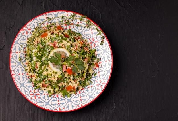 Tabule - orientalischer salat, vorspeise auf einem schwarzen hintergrund.