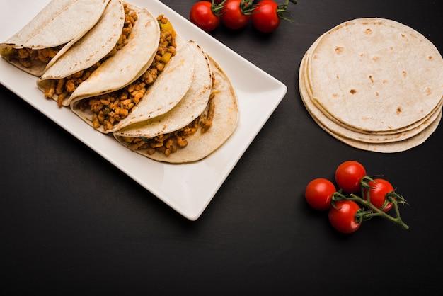 Taco auf teller in der nähe von tomaten