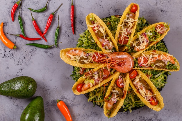 Tacos mit garnelen, salat, käse und jalapeno.