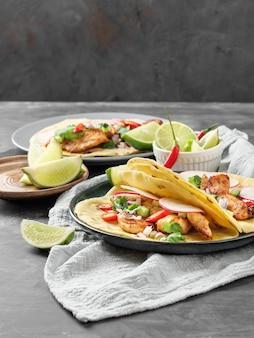 Tacos mit hühnchen, gemüse und kalk auf dem tisch. platz kopieren.