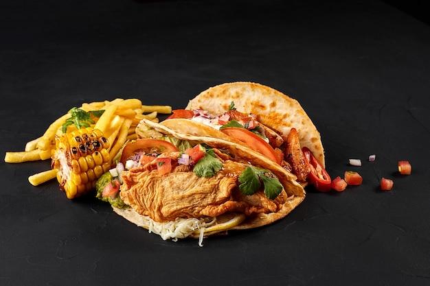 Tacos mit hühnertomate und frischem gemüse und remoulade auf schwarzem hintergrund