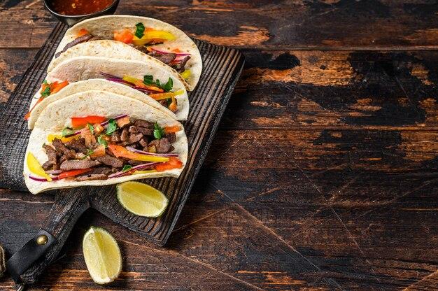 Tacos muscheln mit schweinefleisch, zwiebeln, tomaten, paprika und salsa. mexikanische nahrung. dunkler holztisch. draufsicht.