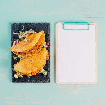 Tacos und klemmbrett auf blauem hintergrund