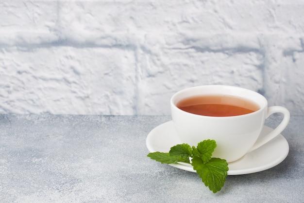 Tadelloser tee in einer weißen schale mit frischen tadellosen blättern.
