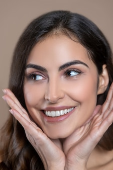 Tadelloses aussehen. gesicht der gut aussehenden jungen lächelnden frau mit braunen augen, die zur seite schauen und ihre handflächen nahe dem kinn halten