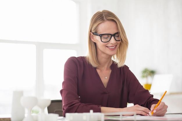Tägliche routine. nachdenkliche fröhliche geschäftsfrau, die eine brille trägt, während sie sich abnutzt