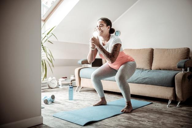 Tägliche trainingseinheit. lächelnde kurvige dame, die breite kniebeugen macht, während sie den unteren teil ihres körpers in ordnung bringt