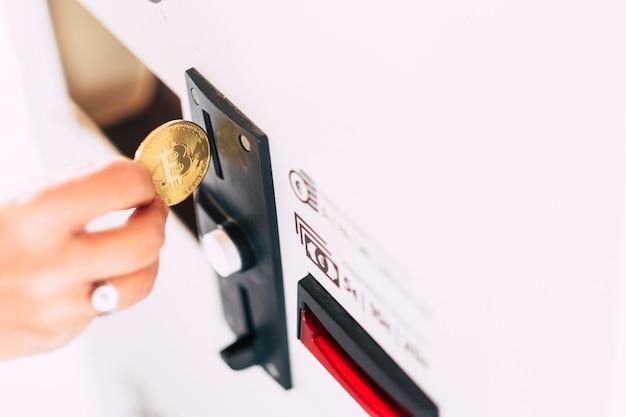 Tägliches geld verwendet automaten, die bitcoin von hand einwerfen, um dienstleistungen zu bezahlen und zu kaufen