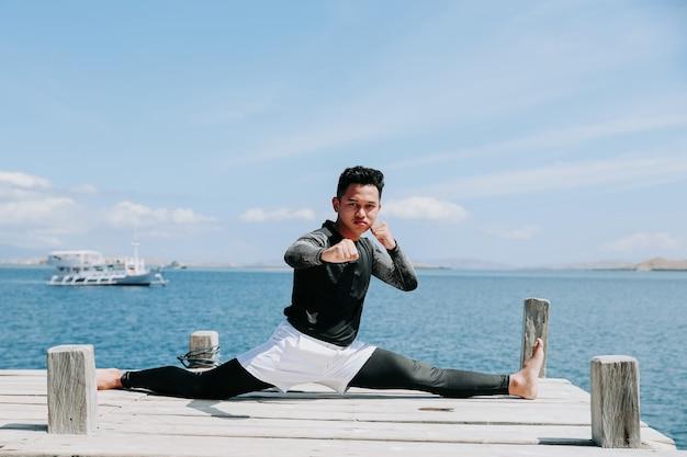 Taekwondo-typ, der mit gespaltenen beinen sitzt, mit meereshintergrund