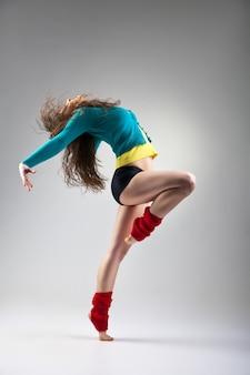 Tänzer im modernen stil posiert auf grauem hintergrund