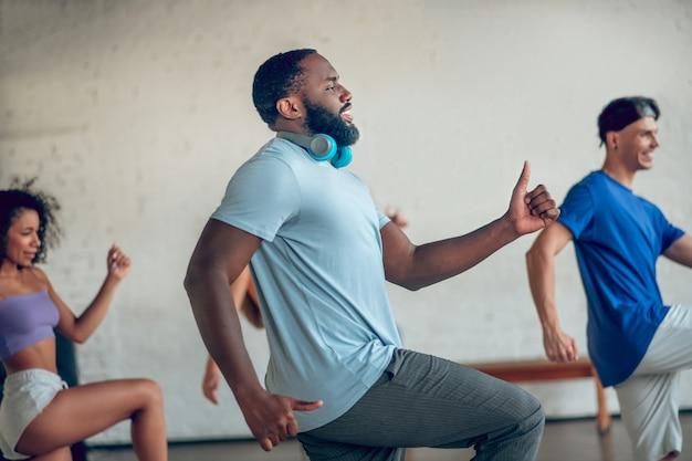 Tänzer. im profil bärtiger dunkelhaariger mann mit kopfhörern und jungen leuten hinter dem tanzen, die synchron sein bein und seine arme bewegen