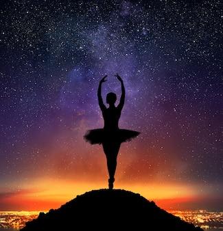 Tänzerin in einer pose des klassischen tanzes auf spitze auf einem berg