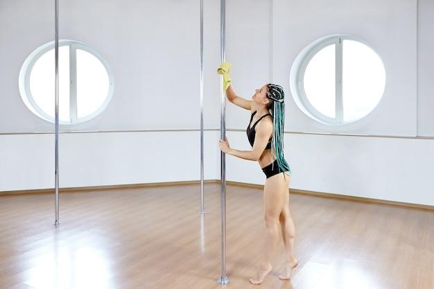 Tänzerin reinigt pole vor dem training im pole dance studio für fitness