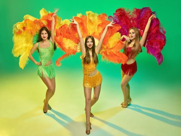 Tänzerinnen posieren auf grüner wand