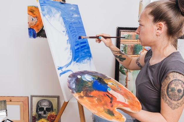 Tätowierte frau, die blaues bild auf segeltuch steht und malt
