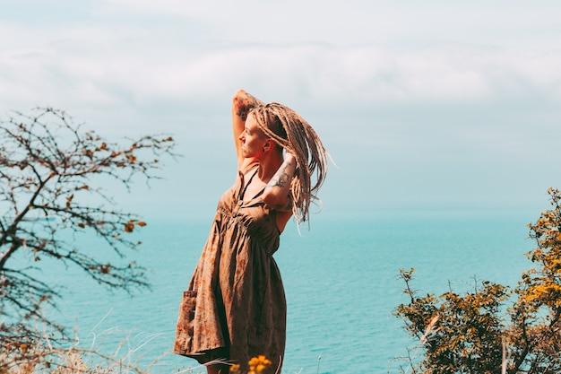Tätowierte frau mit blonden dreadlockssat seereisen und urlaubslebensstil