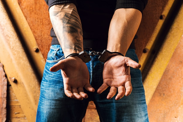 Tätowierte hände eines verbrechers mit handschellen gefesselt