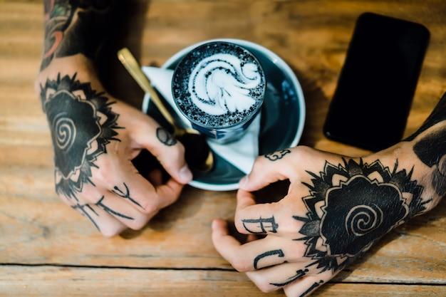 Tätowierte hände. hände halten ein glas mit kaffee.