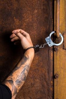 Tätowierte hand eines verbrechers mit handschellen gefesselt