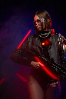 Tätowierte soldatin mit brille und moderner frisur posiert im dunklen hintergrund mit lichtern. glamour und zugleich gefährliche frau mit kybernetischer schulter.
