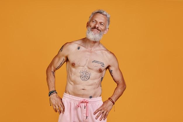 Tätowierter älterer mann mit nacktem oberkörper, der wegschaut und lächelt