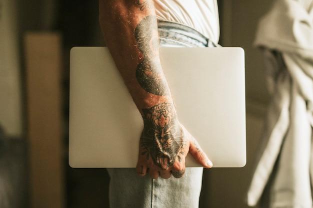 Tätowierter alternativer mann, der einen laptop trägt