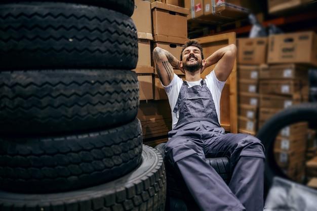 Tätowierter arbeiter, der auf reifen im lager der import- und exportfirma sitzt