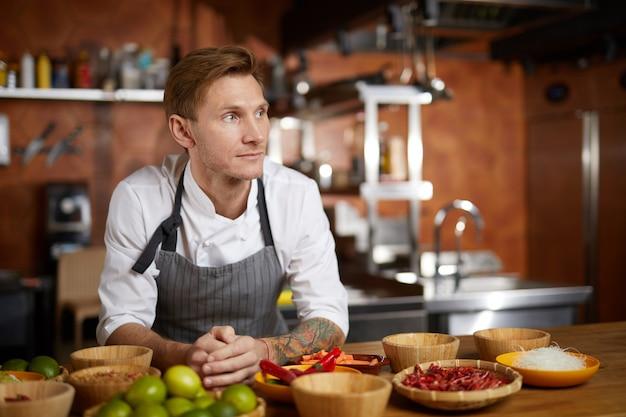 Tätowierter chef, der in der küche aufwirft