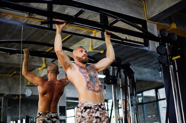 Tätowierter fit mann, der übungen im fitnessstudio macht