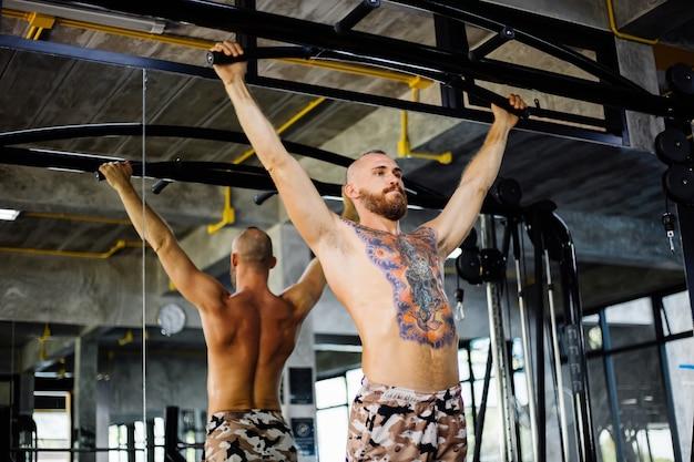 Tätowierter fitter mann, der übung im fitnessstudio macht