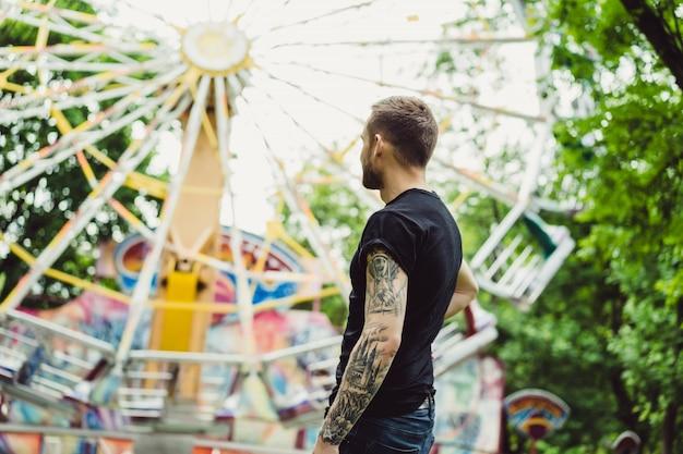 Tätowierter junger mann in einem vergnügungspark auf dem hintergrund eines karussells