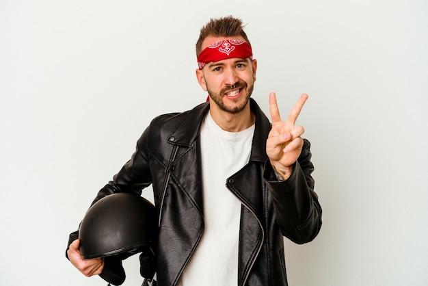 Tätowierter kaukasischer mann des jungen bikers, der einen helm hält, der auf weißem hintergrund lokalisiert ist und nummer zwei mit den fingern zeigt.