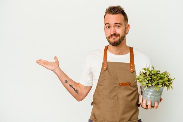 Tätowierter kaukasischer mann des jungen gärtners, der eine pflanze lokalisiert auf weißem hintergrund hält, der einen kopienraum auf einer handfläche zeigt und eine andere hand auf taille hält.