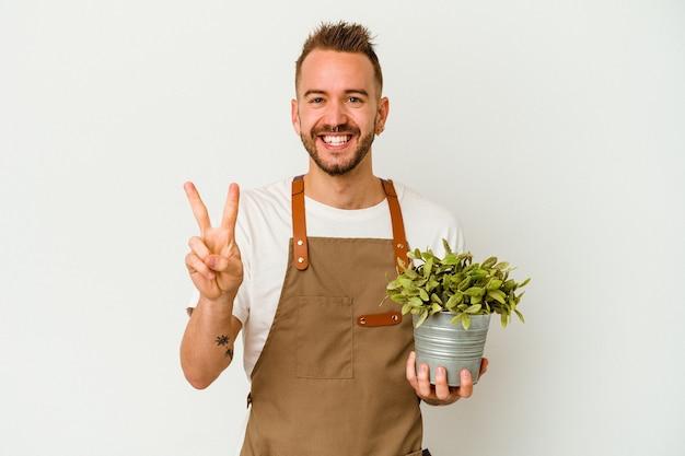 Tätowierter kaukasischer mann des jungen gärtners, der eine pflanze lokalisiert auf weißem hintergrund hält, der nummer zwei mit den fingern zeigt.
