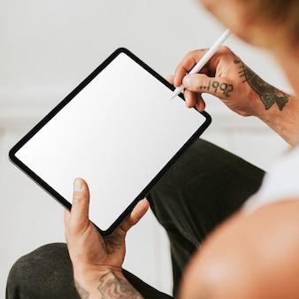 Tätowierter mann, der an tablet-bildschirmmodell arbeitet