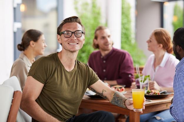 Tätowierter mann, der das mittagessen mit freunden im cafe genießt